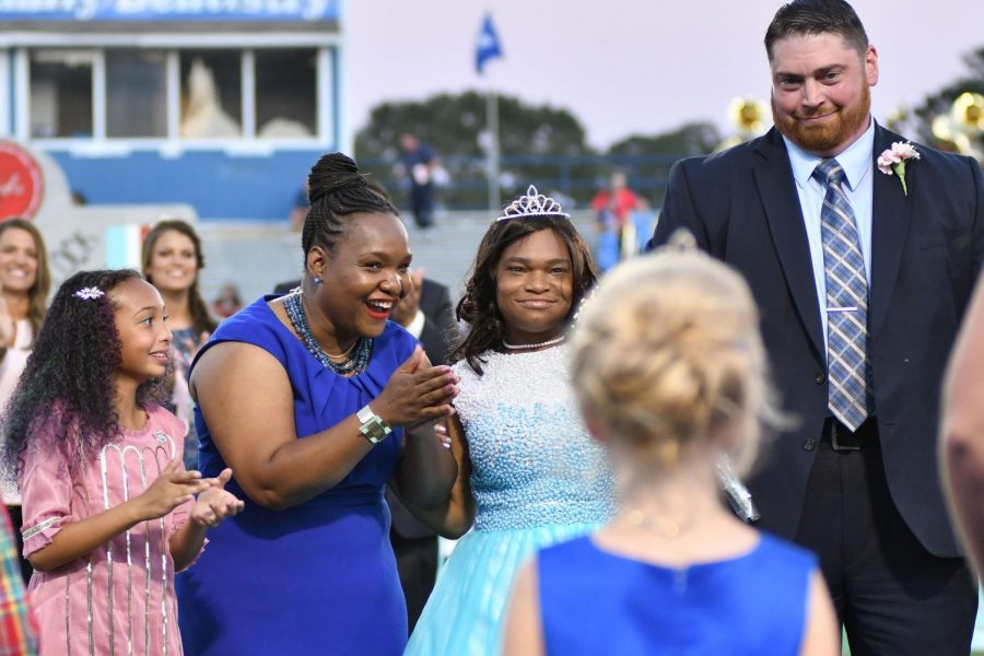 Accompanied by her family, 2017 homecoming queen India Stewart smiles after being crowned.