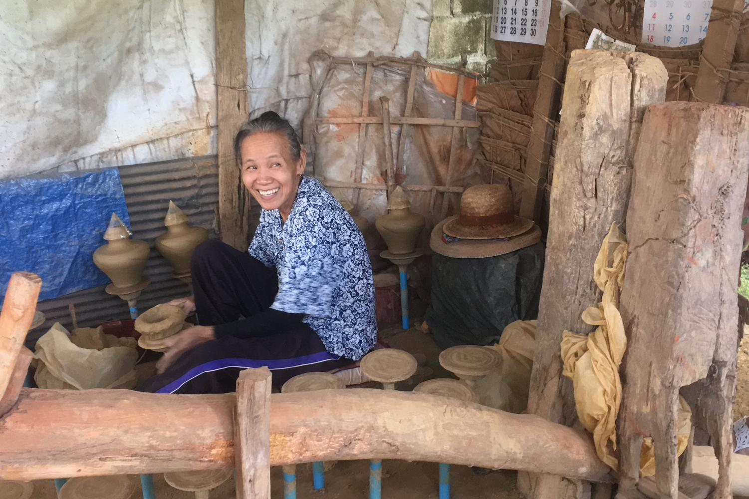 A women sits at her pottery wheel, smiling after someone complimented her work.