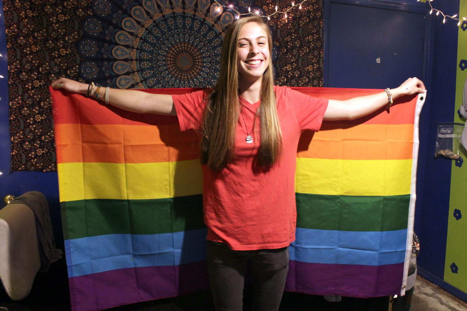 Senior Emily Clark holds up a pride flag.