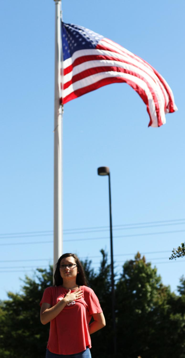 Standing in front of the flag pole, senior Jaiden Kubana recites the pledge in