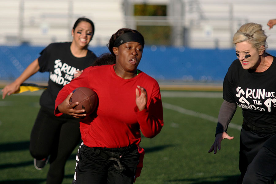 Running to the end zone in the Powderpuff game Nov. 2, senior Kalia Walker sprints past teachers Jennifer James and Mital Kilburn.