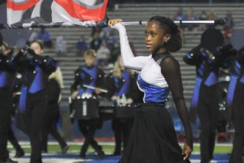 Looking toward the crowd, sophomore Summer Quarles spins her flag during the halftime performance on Sept. 25. The shows theme this year was The Technicolor Klavier.