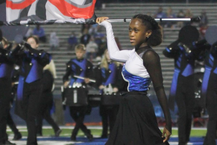 Looking toward the crowd, sophomore Summer Quarles spins her flag during the halftime performance on Sept. 25. The show