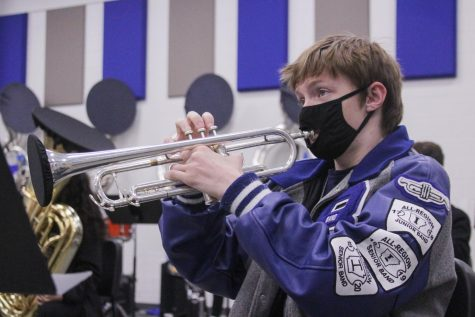 Wearing his band letter jacket, senior Stephen Snow plays his trumpet in Wind Symphony rehearsal Dec. 1. Snow made first band, ninth chair in All-Region auditions this year. When people ask me how hard I practiced when it came to All-Region, I tell them I spend hours and hours going over the music, but the truth is that Im just built different, Snow said.