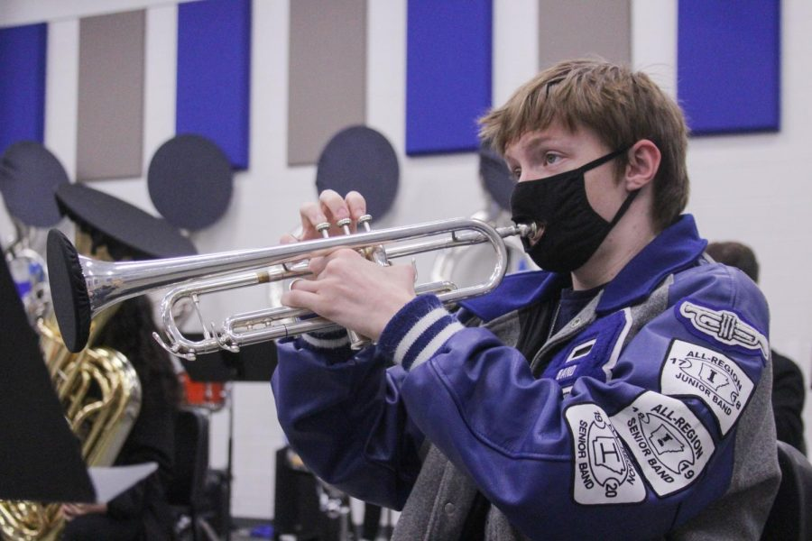 "Wearing his band letter jacket, senior Stephen Snow plays his trumpet in Wind Symphony rehearsal Dec. 1. Snow made first band, ninth chair in All-Region auditions this year. ""When people ask me how hard I practiced when it came to All-Region, I tell them I spend hours and hours going over the music, but the truth is that I"